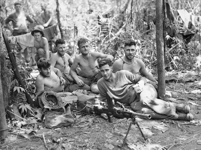 Eight young soldiers rest on the ground, most of them shirtless. A Bren gun on a bipod is in the foreground.