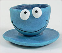 A blue clay model of a cup and saucer.