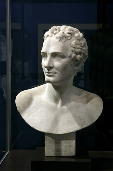 White bust of Cook against a blue background. Cook is shirtless and hatless with curled hair, in the manner of an ancient Greek hero