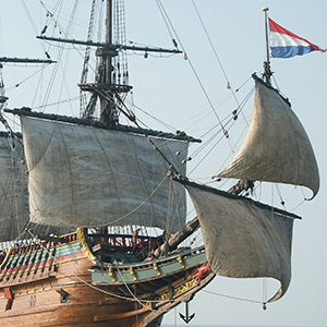 Timber sailing vessel at sea with lower sails catching the wind. The Dutch flag sails from the bowsprit.