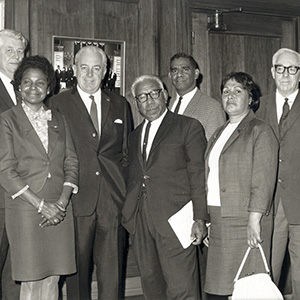 The seven people named stand in front of a wood-panelled wall in what looks like Old Parliament House.
