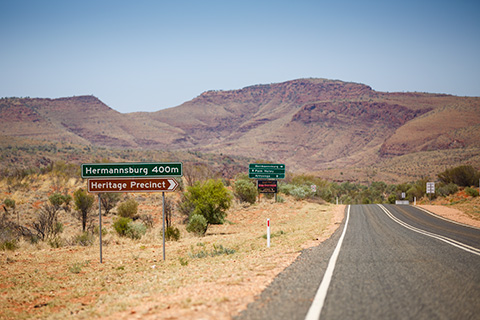 A photo of a road leading towards a mountain.  A signpost at the side of the road reads: 'Hermannsburg 400m, Heritage Precinct'.