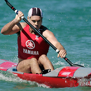 man in red singlet with Yamaha printed on it paddles a surf ski.