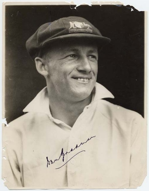 Donald Bradman smiling in a portrait photo, photo is also signed by Bradman