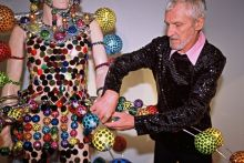 Man in sequined top adjusting colourful adornments on a costume that is worn by a mannequin