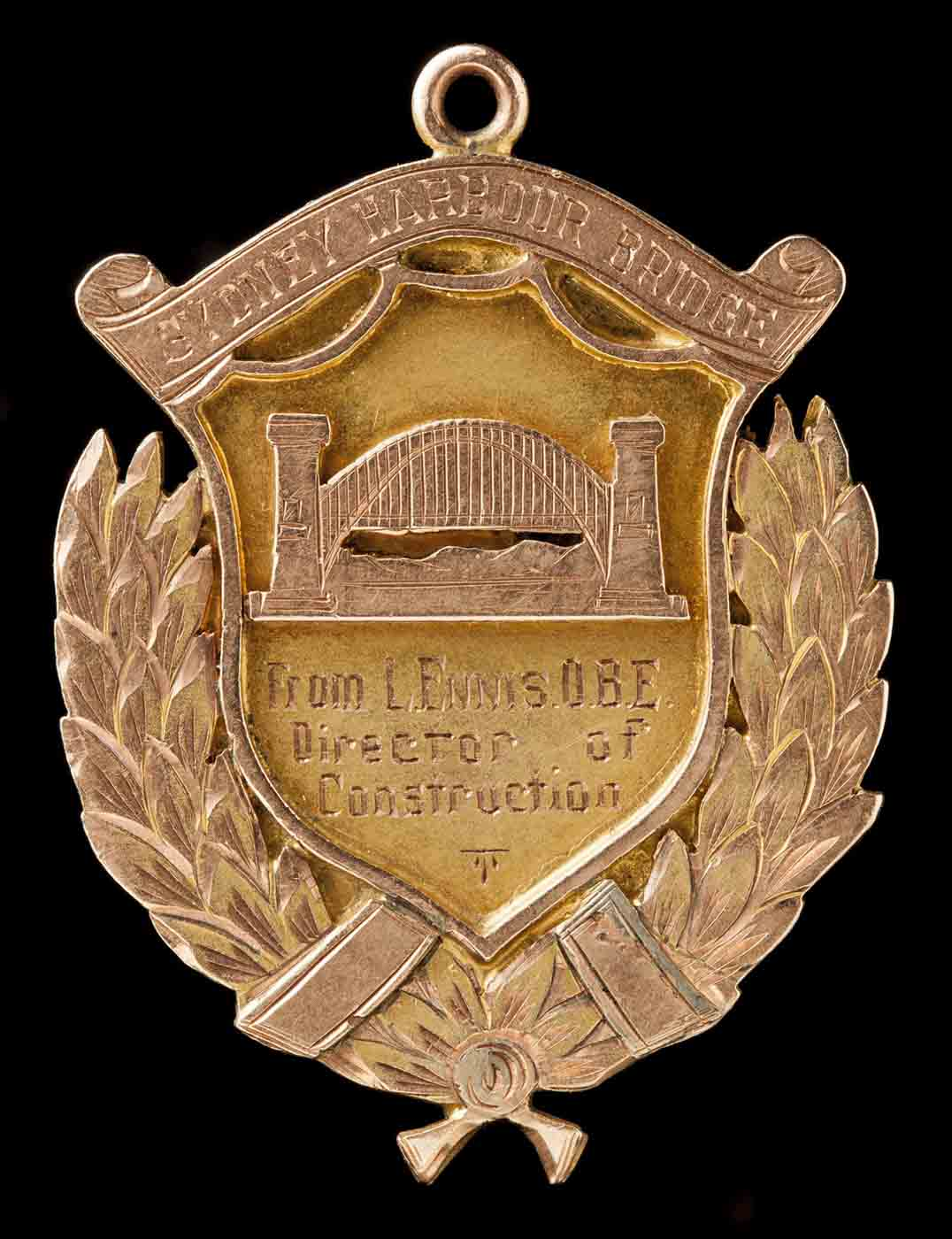 Faded gold-coloured metal badge with an image of the bridge and the words 'From L Ennis OBE, Director of Construction'. - click to view larger image