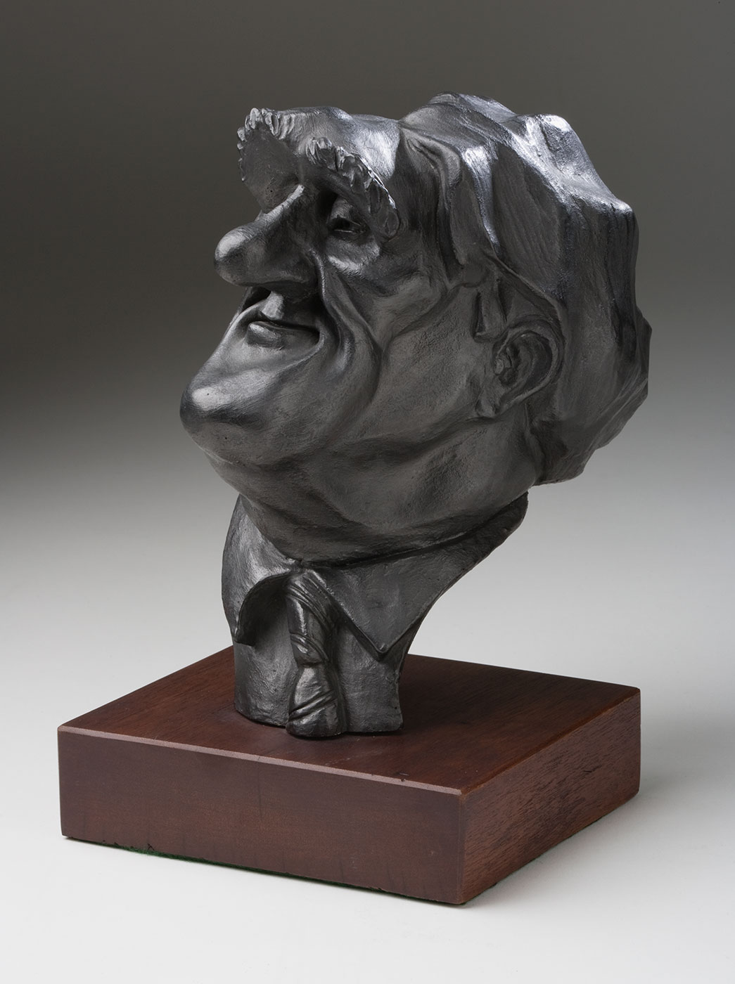 Sculpture titled 'The Dismissal - 20th Anniversary' by John Shakespeare. Three-dimensional comical figures of Opposition Leader Malcolm Fraser, Governor General Sir John Kerr, and Prime Minister Gough Whitlam are mounted on a piece of black painted board. The figure of Kerr is about to club Whitlam with a bottle of Champagne, while Fraser holds Kerr's coat tails. - click to view larger image