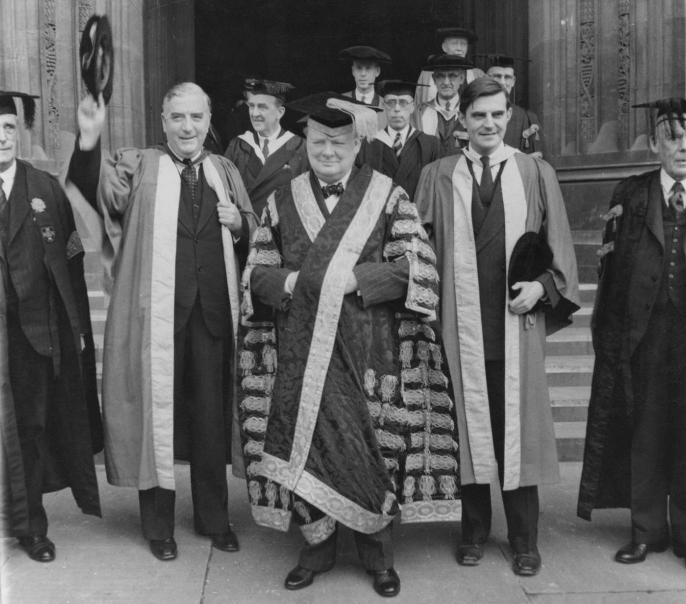 A black and white photo of a group of older men dressed in graduate garb