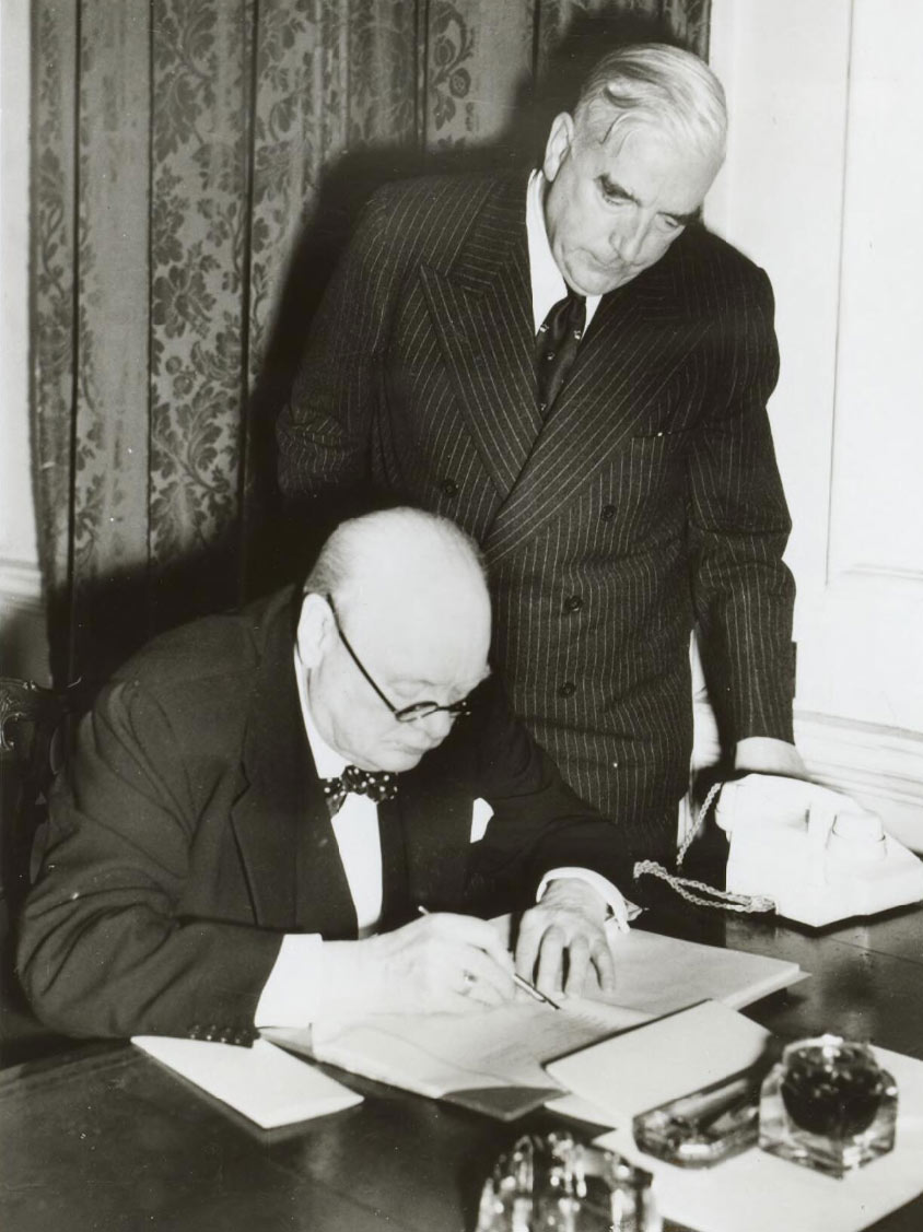 Churchill is at a desk examining some documents. Menzies is standing beside him, looking over his shoulder. - click to view larger image