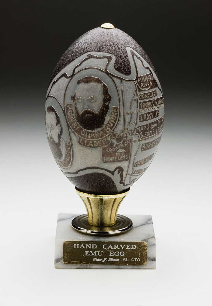The egg, carved by craftsman Peter Harris, depicts a map of the journey of Burke and Wills. The egg rests on a marble base with a gold-plated plaque. The engraved text reads 'HAND CARVED / EMU EGG / Peter J. Harris GL 470'. - click to view larger image
