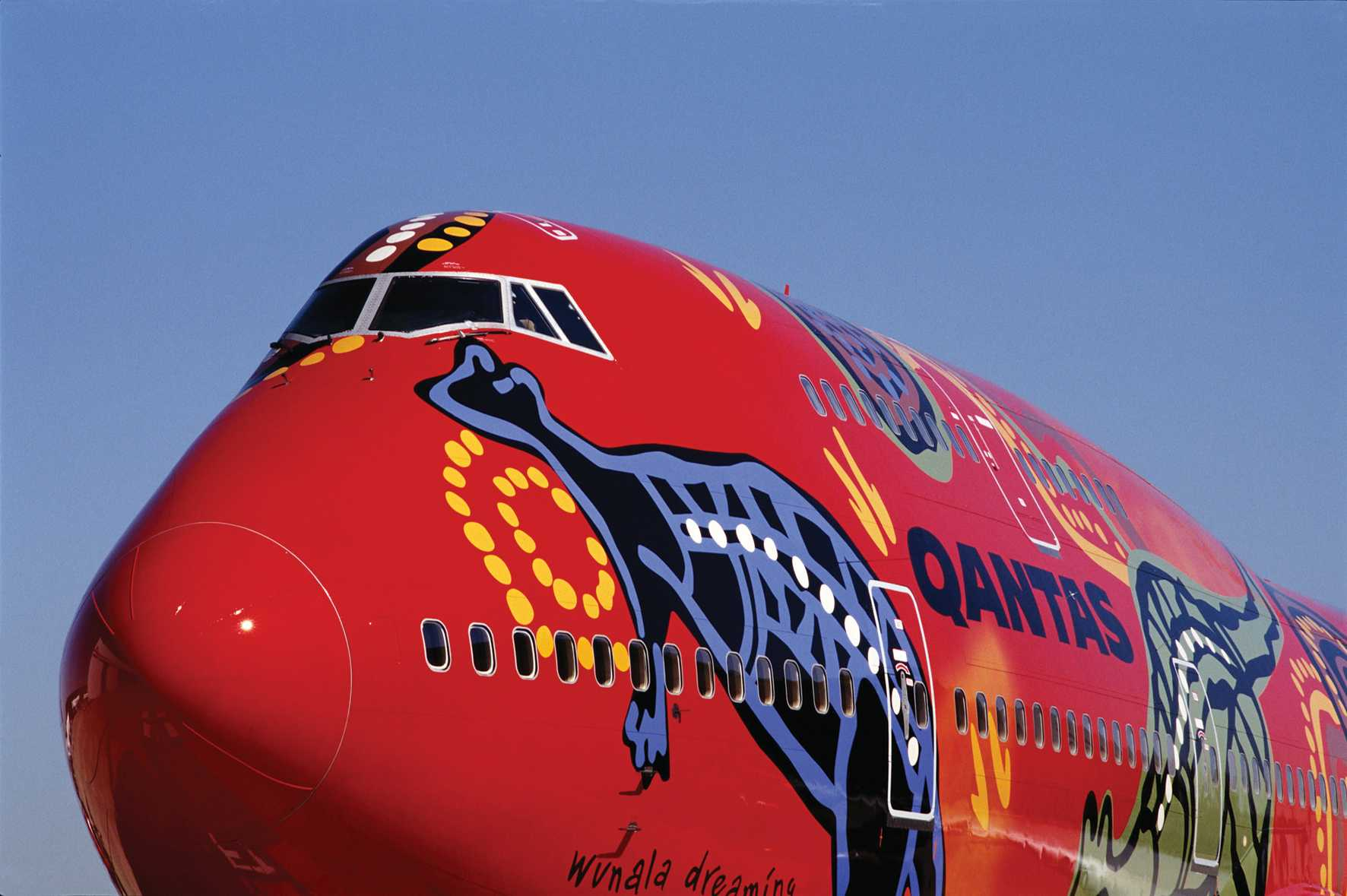 Front of a large aeroplane, painted in Aboriginal designs on a red backdrop. - click to view larger image