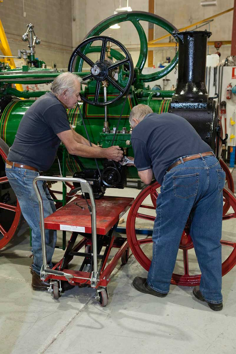 A colour photograph of two men working on a large steam engine. - click to view larger image