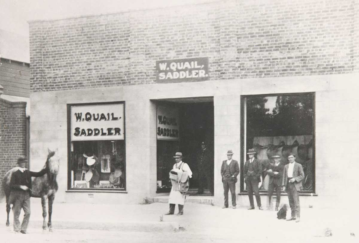 William Quail carrying a saddle outside his shop in Cooma to fit on a horse being held with four men standing outside the shop