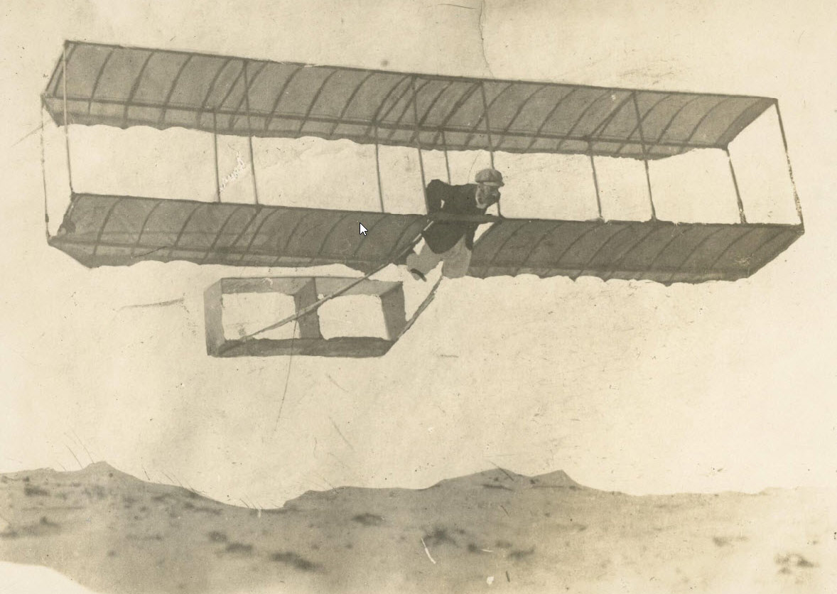 A biplane glider being flown above a sand dune. - click to view larger image