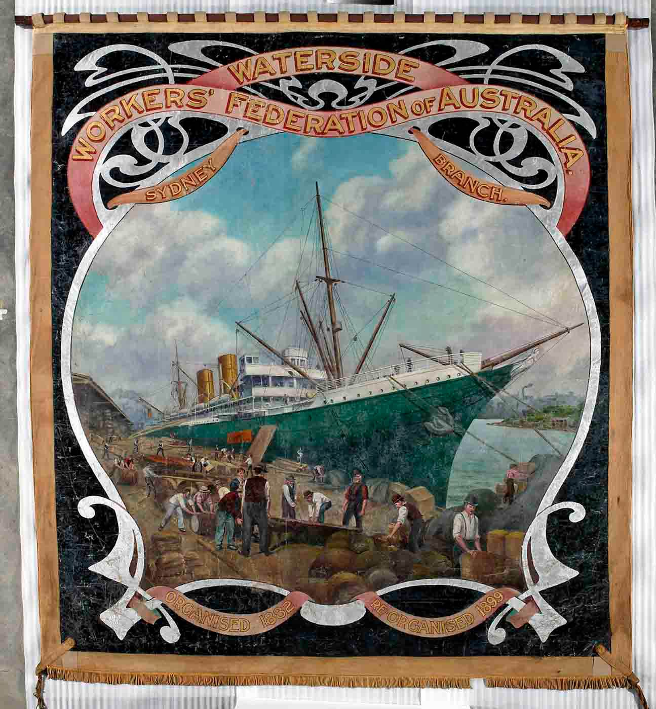 Large almost square banner painted in oil colours, showing a central image of a ship docked beside a busy wharf. 'Waterside Workers' Federation of Australia' and 'Sydney branch' is written at the top. At the bottom the text reads 'Organised 1882', 'Re-organised 1899'.