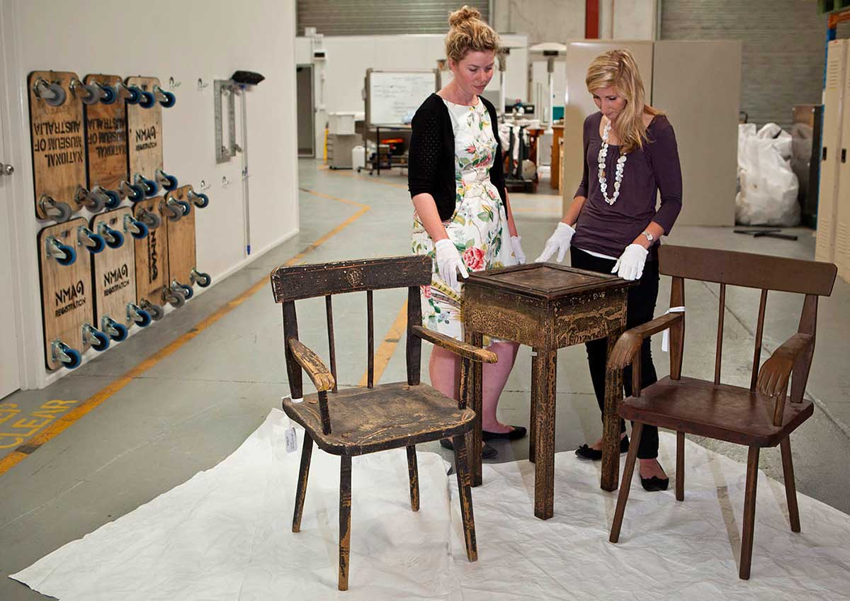 Two women stand behind a small wooden table and two chairs in a warehouse.