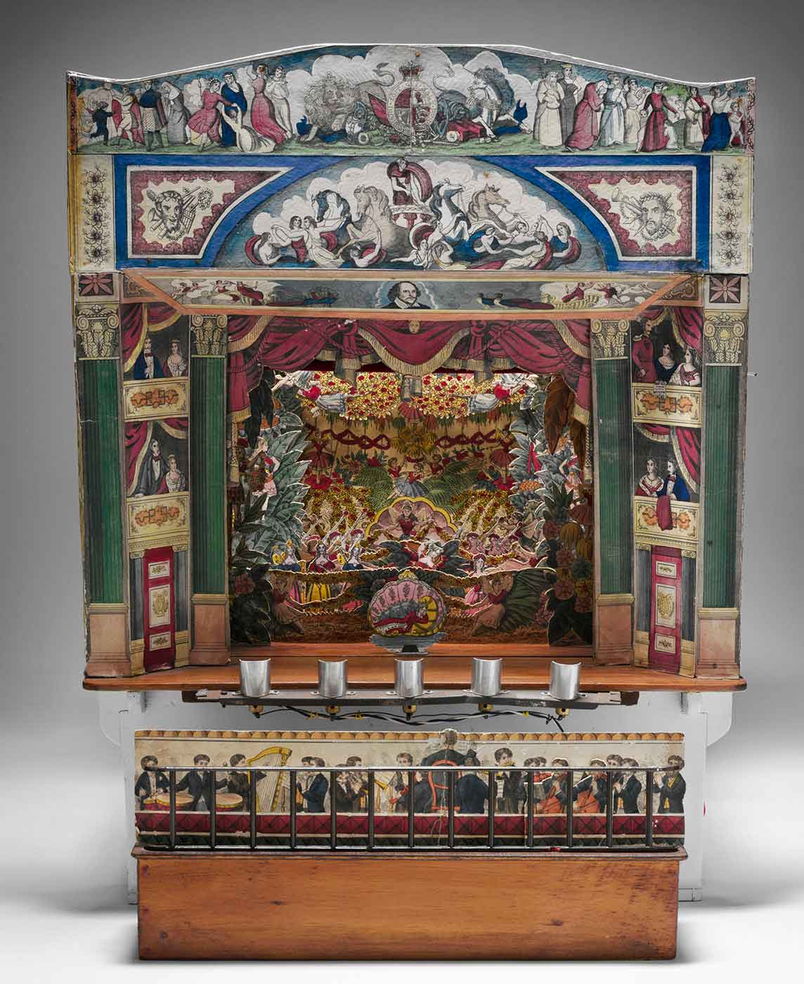 Front view of a brightly coloured toy stage, with cardboard sets and characters, and row of silver candle holders below. - click to view larger image