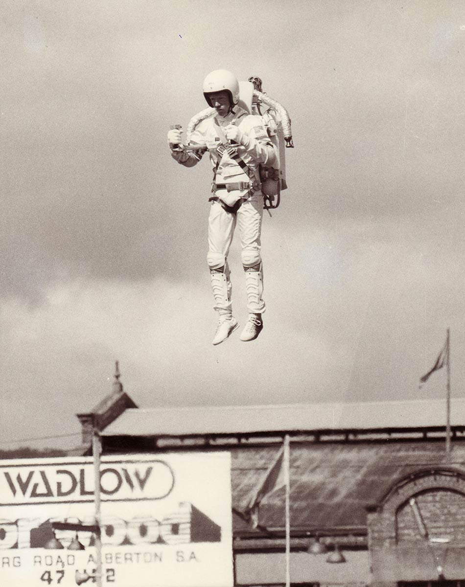A man with a jetback on his back rises into the air. He wears a helmet and white suit. - click to view larger image