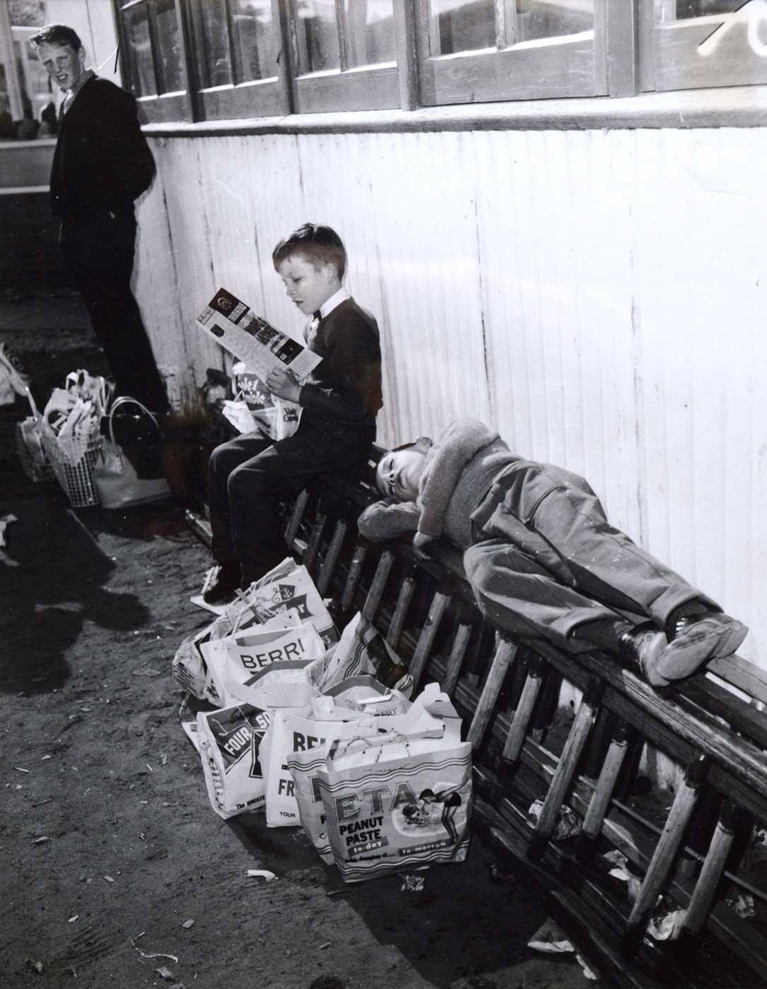 Black and white photograph showing two young boys, one lying with his eyes closed, on a ladder which rests longways, alongside a wall. Several show bags are lined up beneath him. Beside him, another boy sits reading. - click to view larger image