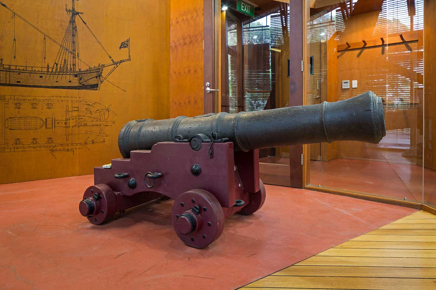A large cannon mounted on a timber base, on display in a museum.   - click to view larger image