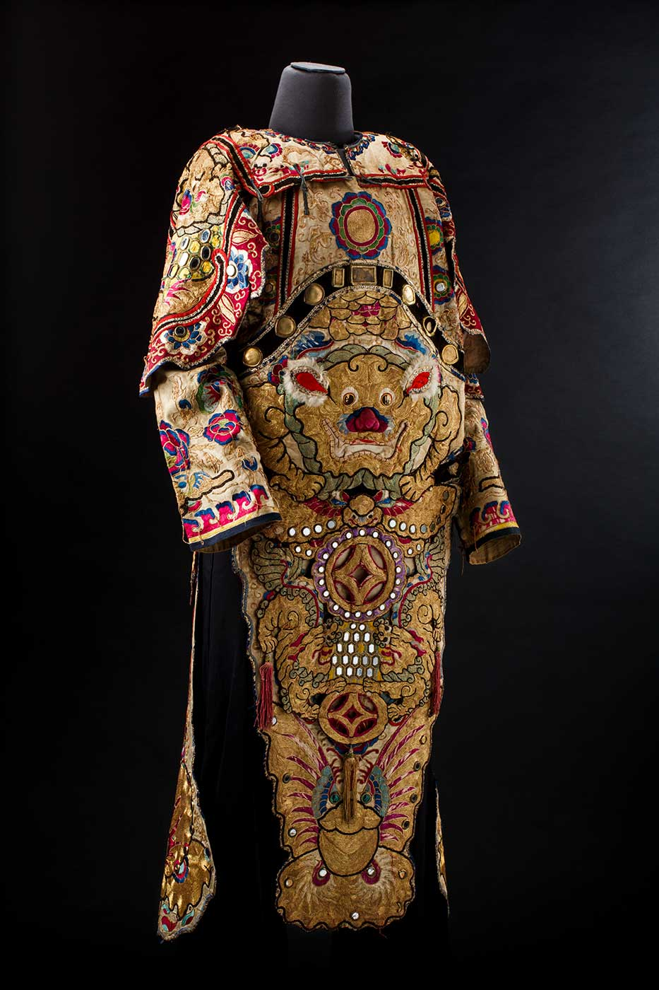 Colour photograph of a multi-coloured embroidered garment on a mannequin.  - click to view larger image