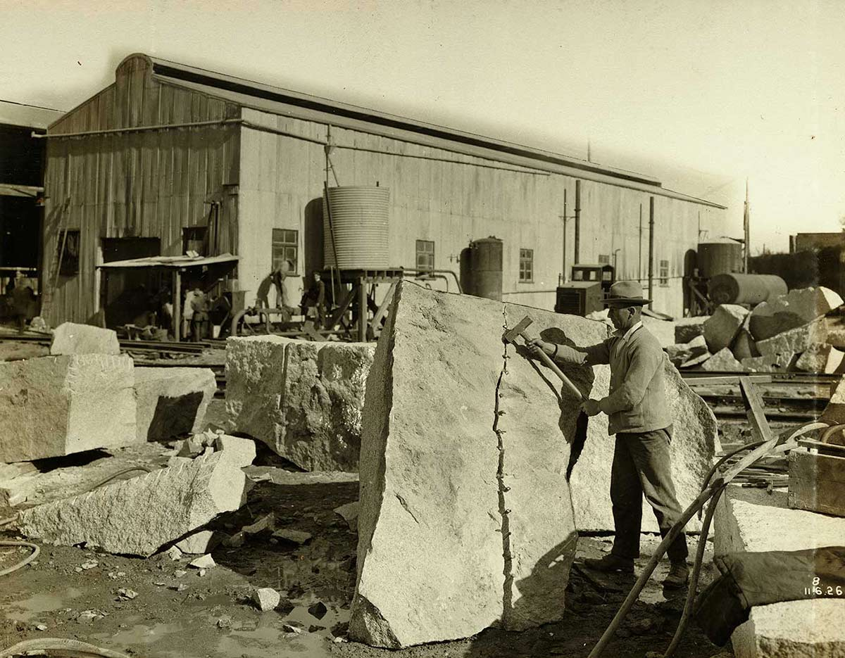 A worker uses wedges and a hammer to split a granite block. - click to view larger image