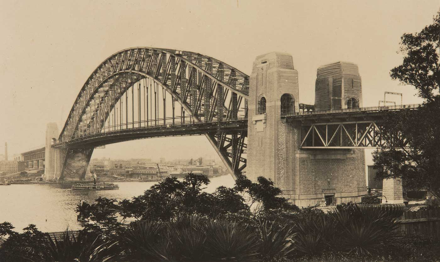 A black and white photograph of the Sydney Harbour Bridge, with a steam ferry passing under it. - click to view larger image