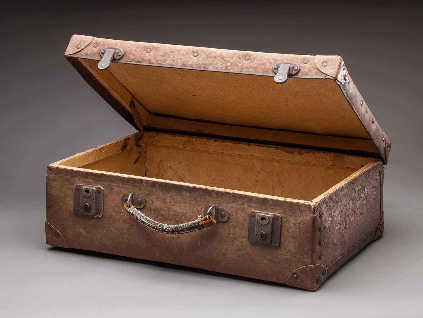 Colour photograph of a brown vinyl suitcase with the lid partially open. It has reinforced corners, a worn handle and two metal clasps at the front. - click to view larger image