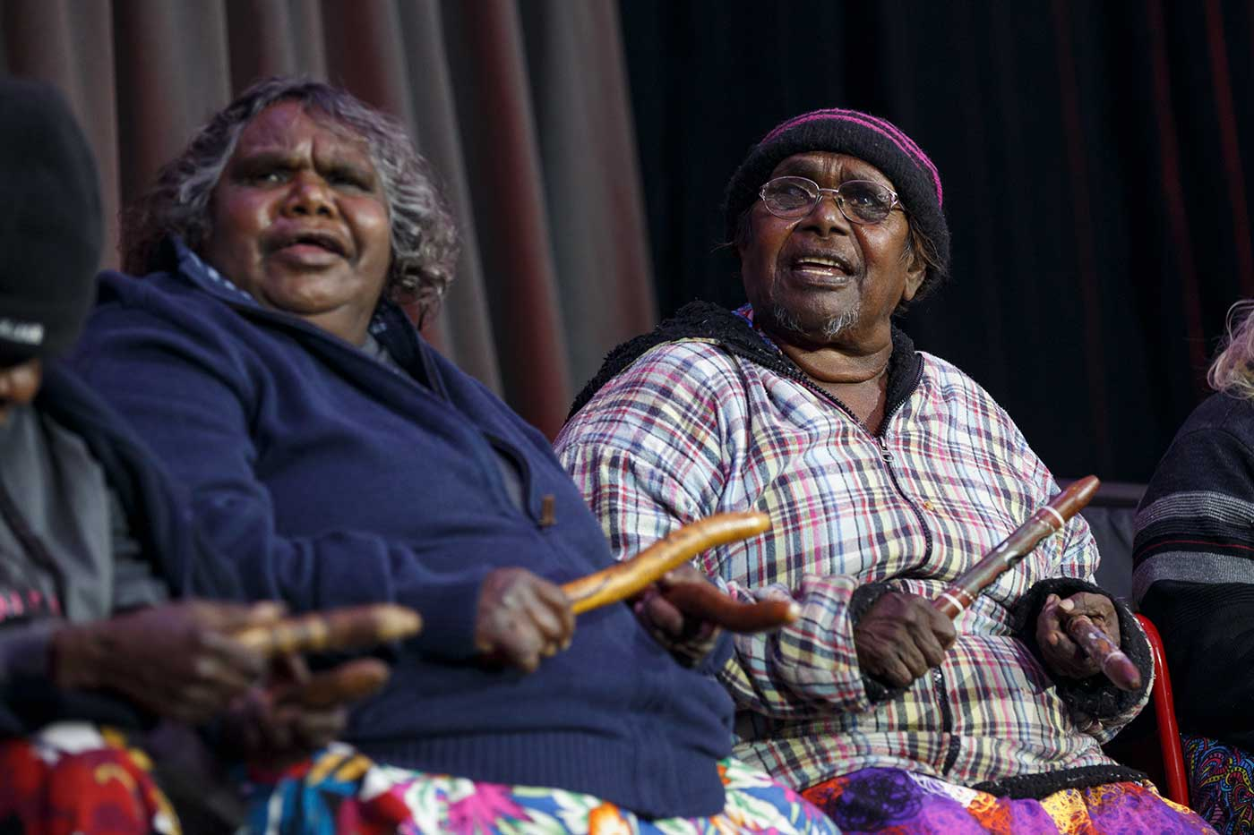 Seated women with wooden clap sticks - click to view larger image