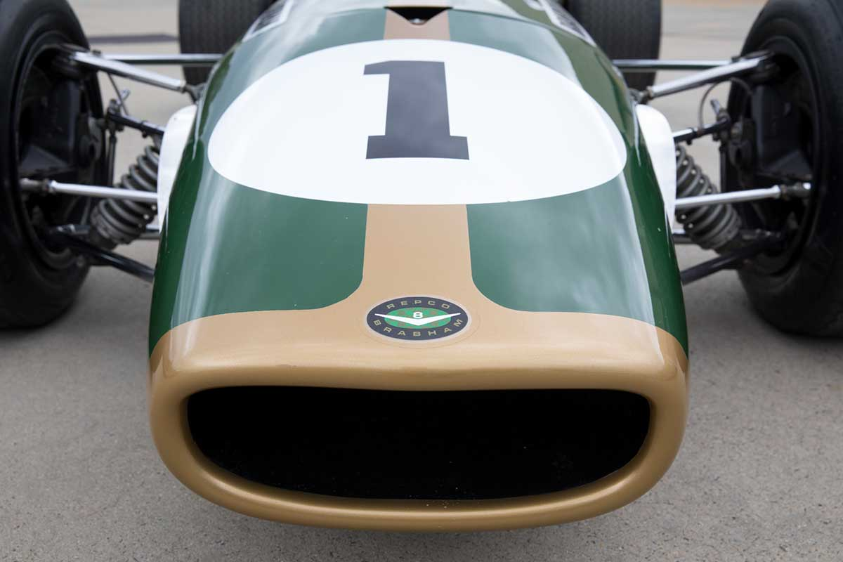 Detail showing part of racing car nose cone in dark green with gold trim. - click to view larger image