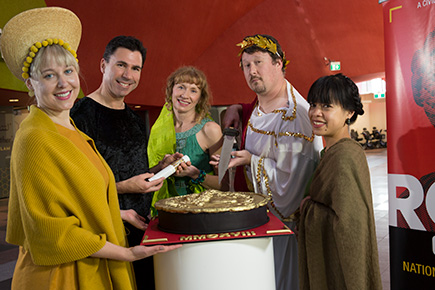 A small group of people dressed in costume surround a decorative cake in the form of a Roman coin