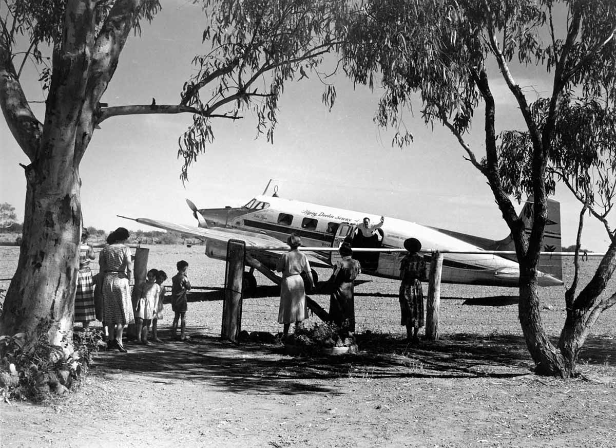 A black and white photo of a plane inside a paddock. There are several people, including children, on the other side of the fence facing the plane.