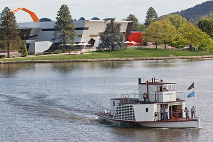 A paddle steamer cruises a body of water. In the background is a contemporary building and trees.