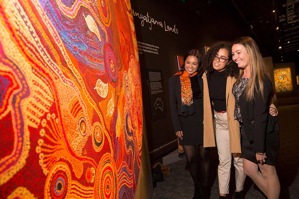 Three women admire a circular painting in the 'Songlines' exhibition.