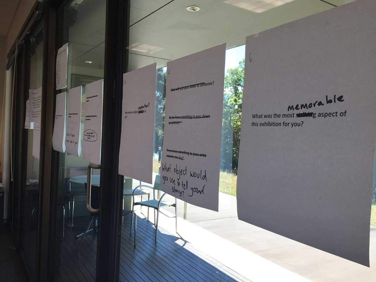 Sheets of paper with questions on them stuck to a glass wall.