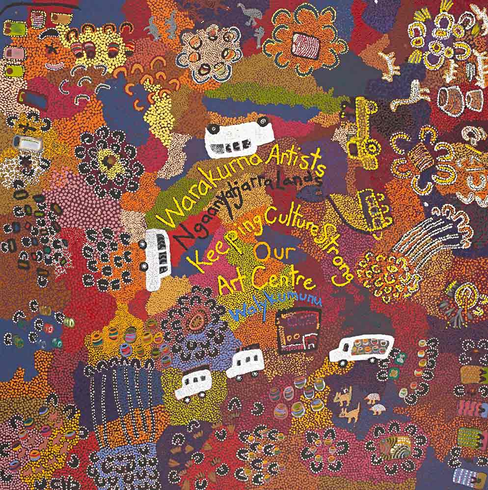 A multi-coloured dot painting with three motor vehicles painted in white in the centre and another two in yellow dots on the right hand side. 'Warakurna Artists/ Ngaanyatjarra Lands / Keeping Culture Strong / Our / Art Centre' is written in the central section. - click to view larger image