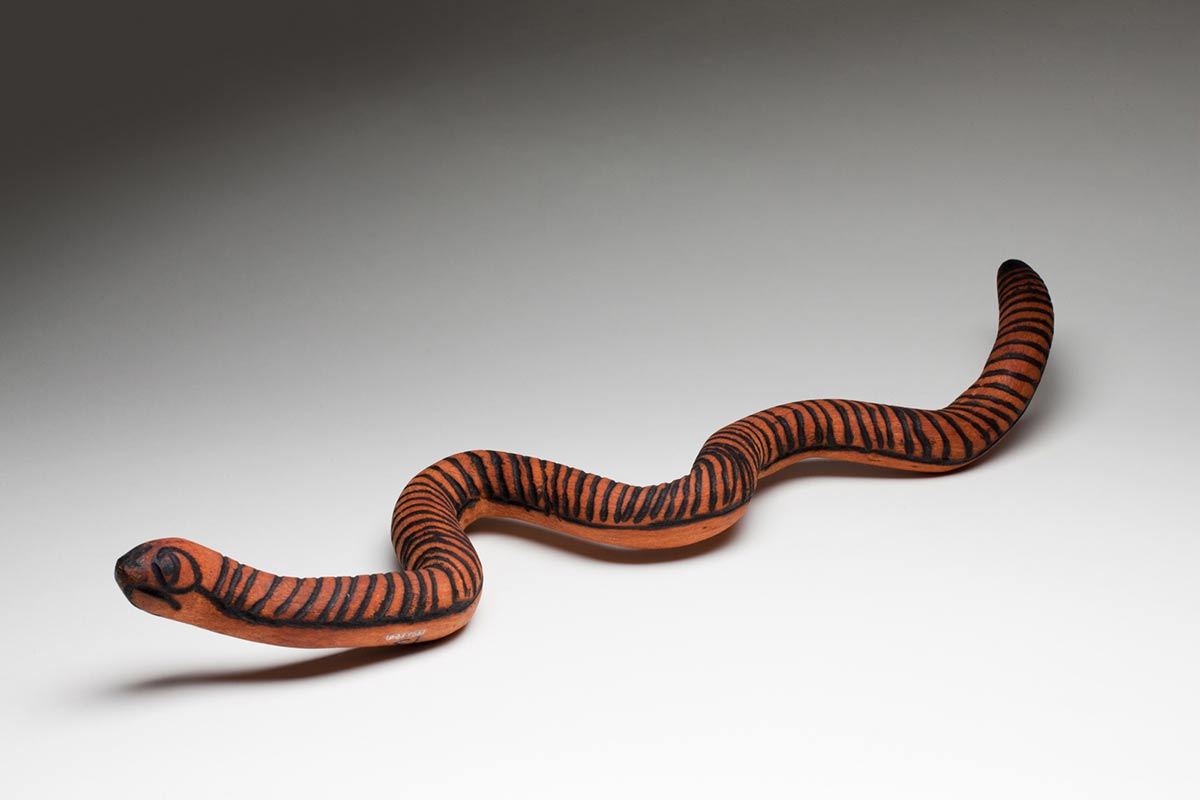Thin wooden sculpture of a snake with its eyes and nostrils burnt into the wood in pokerwork markings and the top of its sinuously curved body covered in pokerwork bands of parallel lines running horizontally to the body. - click to view larger image