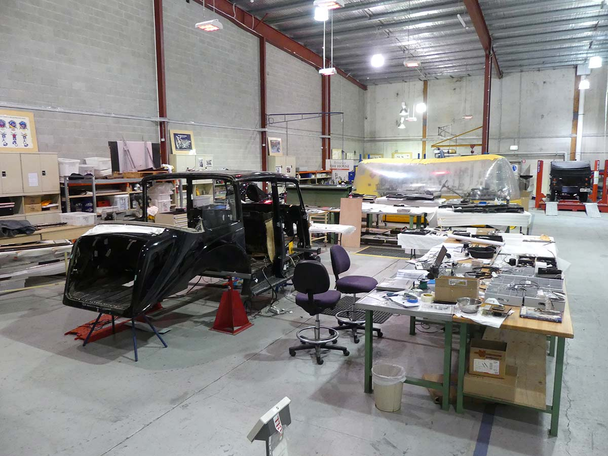 Wide view of a large workshop with part of a car body surrounded by equipment and work tables. - click to view larger image