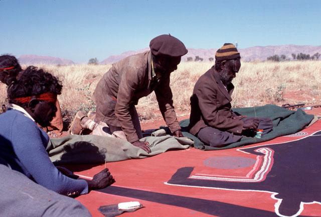 Men working on painting in desert.