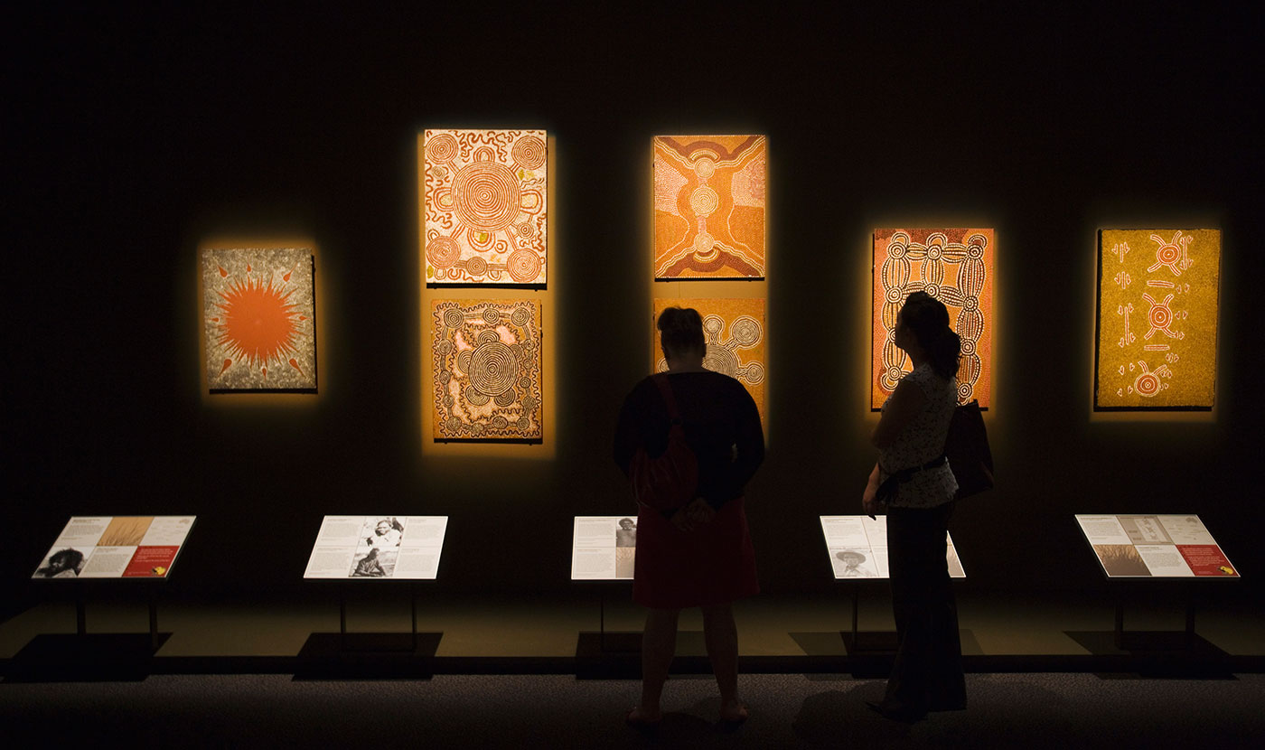 Silhouette of two visitors standing in front of seven Aboriginal dot paintings. - click to view larger image