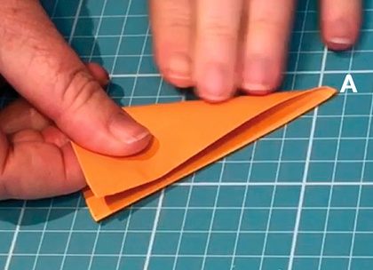 A piece of orange paper which has been partially folder over. Fingers from one hand hold down one side of the paper while the other hand holds a pencil which points to a corner with the capital letter A in white font.