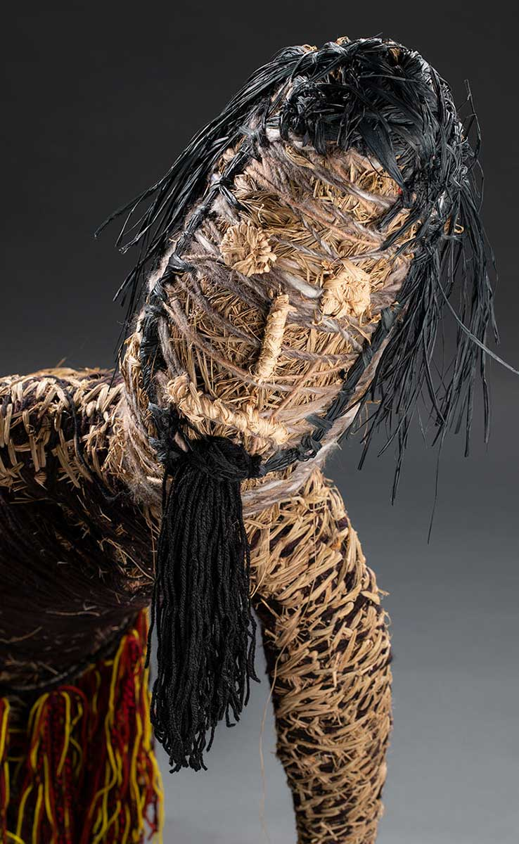 The detail image of a sculpture's male-like face with a long pointy black beard and black hair. The sculpture is made of various plant-based and synthetic materials. - click to view larger image