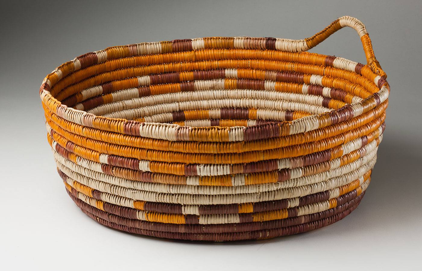 An orange, brown and straw-coloured coil basket made from pandanus fibre and vegetable dyes. It has an 'INJALAK' tag tied to a small handle at the side.