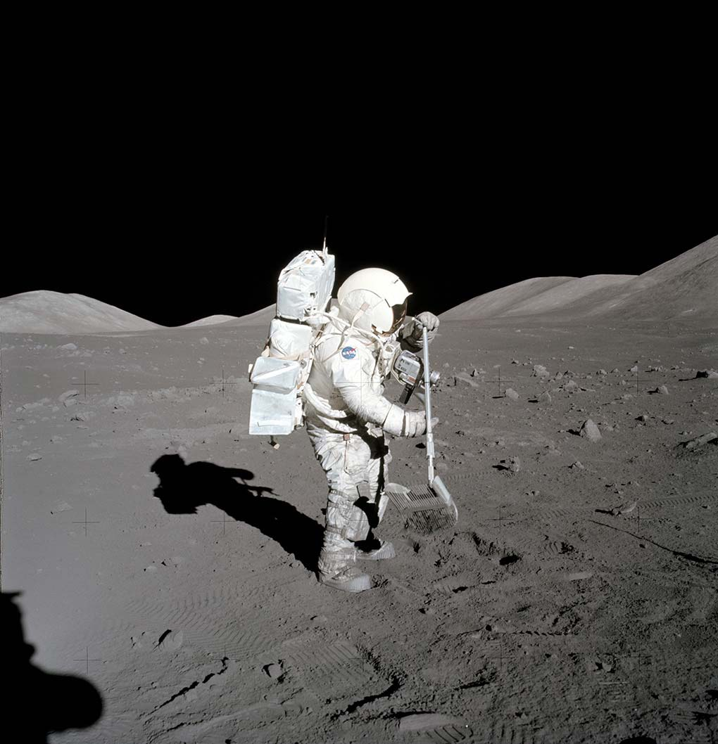 A photograph of an astronaut using a tool for collecting lunar rock samples. - click to view larger image