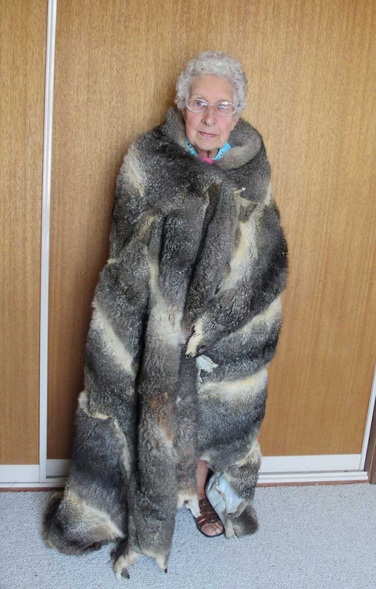 An image of an elderly lady wearing a possum-skin cloak. - click to view larger image