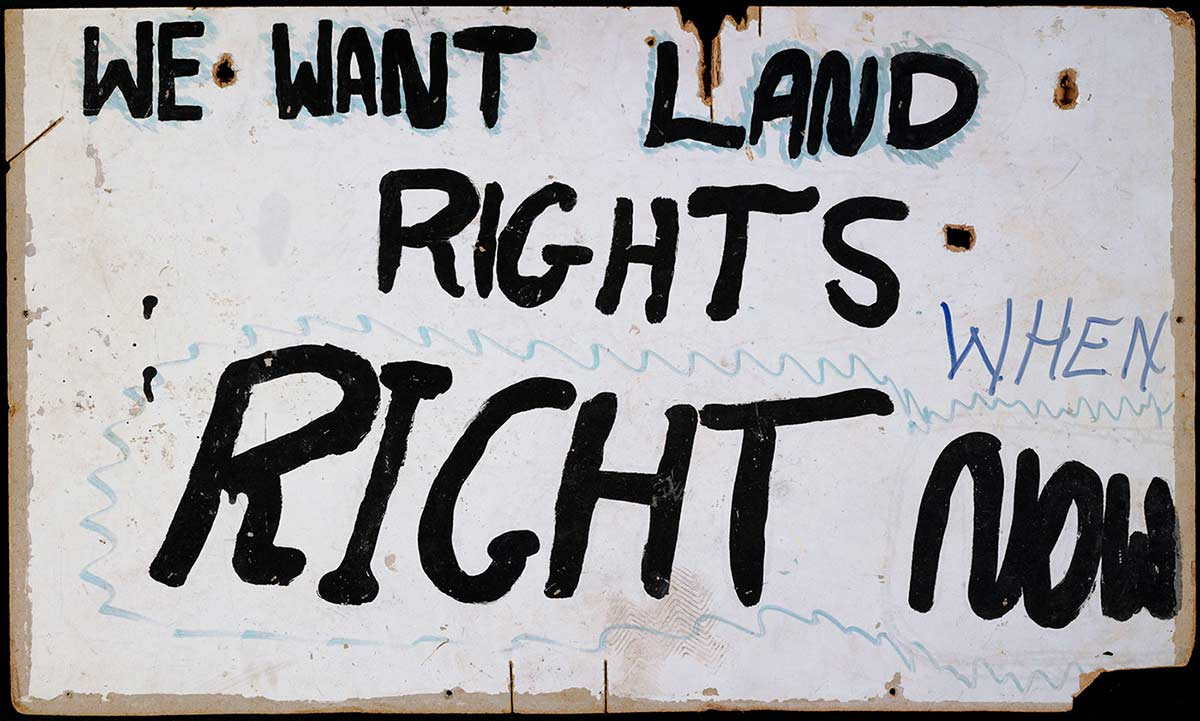 A placard. The text 'WE WANT LAND RIGHTS RIGHT NOW' has been painted in black paint on a rectangular masonite board, with a painted white background. 'WHEN' has been added in purple felt pen. - click to view larger image
