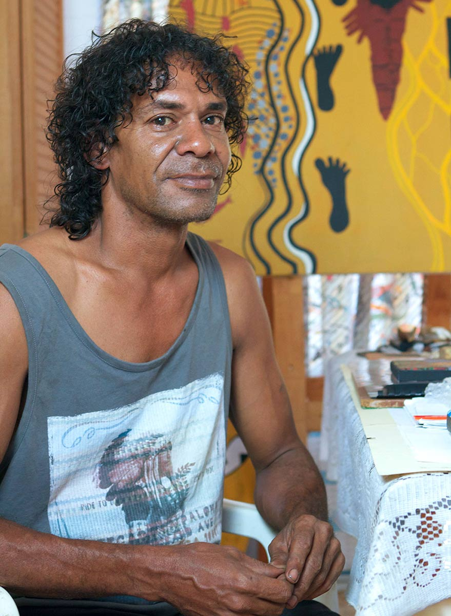 Portrait of an Indigenous Australian man sitting in front of a colourful painting. - click to view larger image