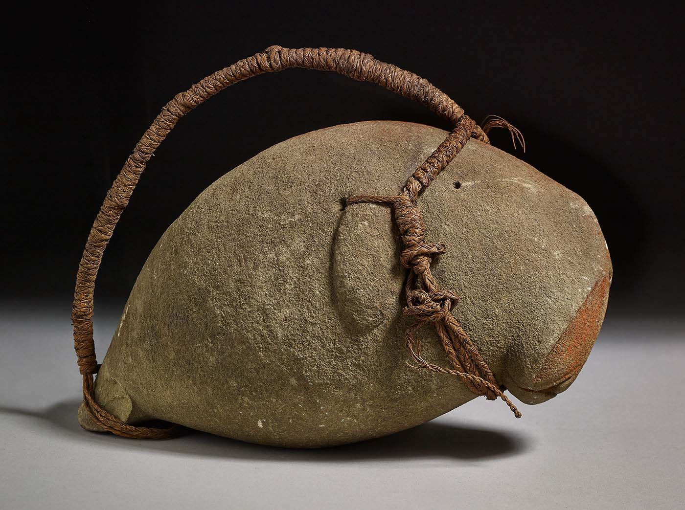 Dugong shaped from grey stone with a cord for suspension and a red ochre strip along the backbone.