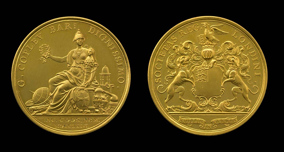 A photograph of the front and back of a gold medal. - click to view larger image