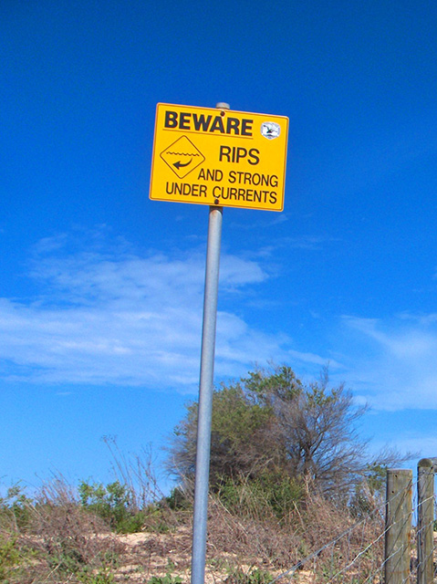 Yellow sign displaying the words 'BEWARE RIPS AND STRONG UNDER CURRENTS'. - click to view larger image